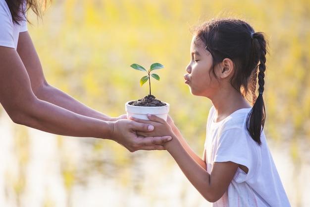 アジアの女の子と彼女の母親が地面に植栽を準備するための植木鉢に若い苗を保持