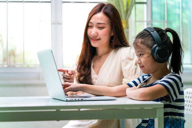 Азиатская девушка и ее мать используют ноутбук для онлайн-обучения во время домашнего обучения дома.