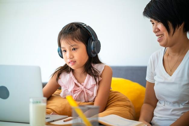アジアの女の子と彼女の母親は、自宅でのホームスクーリング中にオンライン学習のためにラップトップを使用しています。