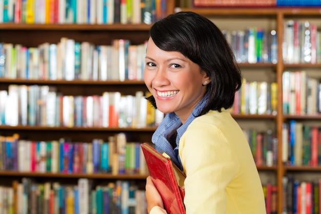 Азиатская девушка в библиотеке держит книгу