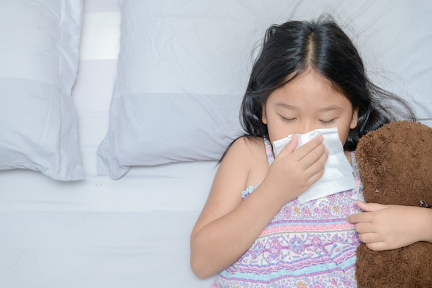 Asian girl blowing the nose by tissue