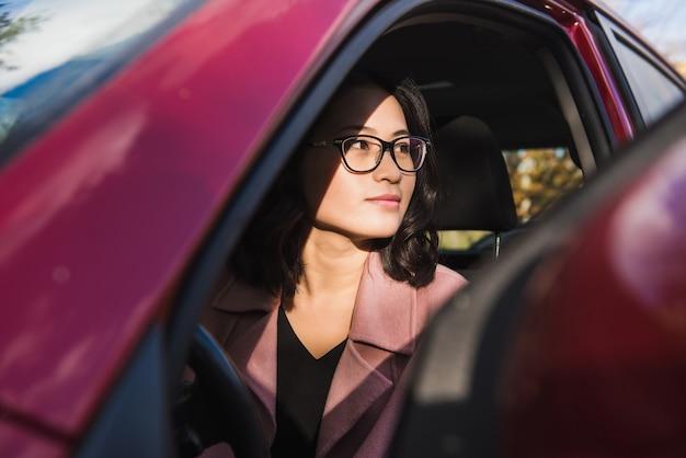Asian girl in the car. girl looks away.