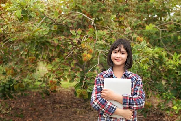 Азиатская девушка проверяя отчет органические фрукты