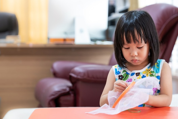 Asian girl child sewing in living room at home as home schooling