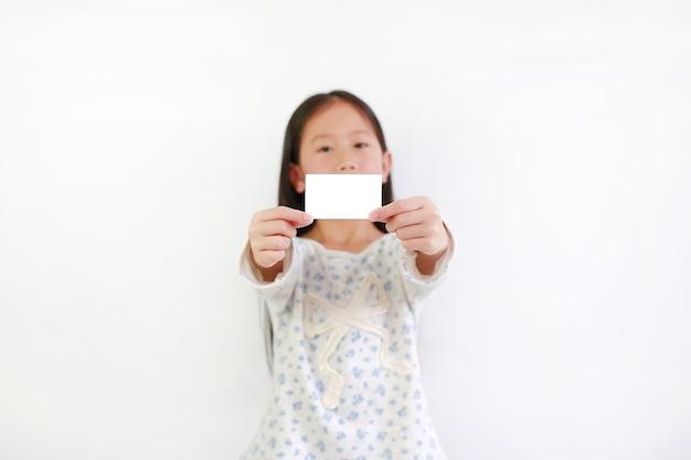 Азиатский ребенок девушки показывая пустую белую карточку над белой предпосылкой. сосредоточьтесь на карте в руках