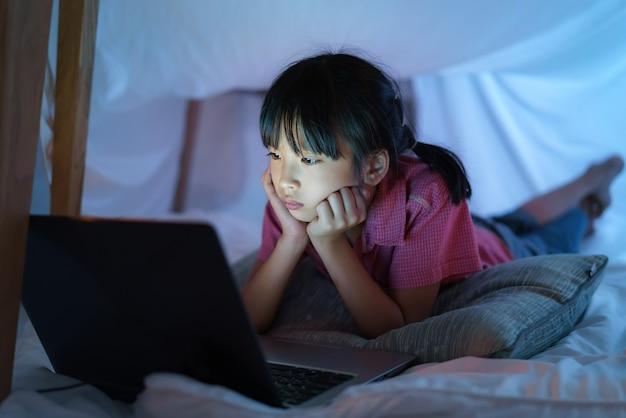 自宅の居間でキャンプの暗闇の中でラップトップで映画を想像的に見て遊ぶキャンプを作るアジアの女児。