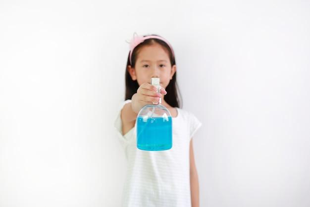 흰색 배경, 방부제에 격리된 코로나바이러스 전염병 발병에 대비하기 위해 병 스프레이 알코올 액체를 사용하는 아시아 여자 아이. 아이 손에 선택적 초점