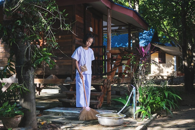 Asian girl cleaning the area of temple in forest , voluntary activities