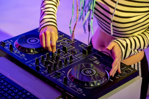 Asian girl dj is playing a turntable in night party is colorful.