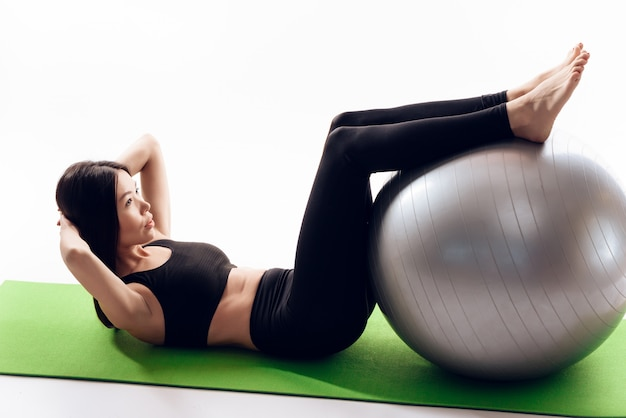 Asian girl does press exercises with gym ball.