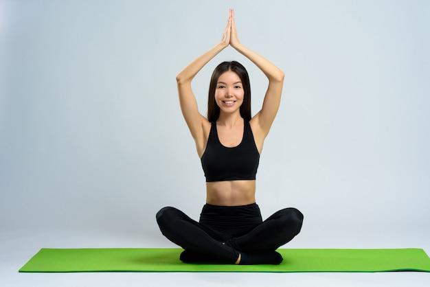 Asian girl does yoga on gym carpet. lotus pose.
