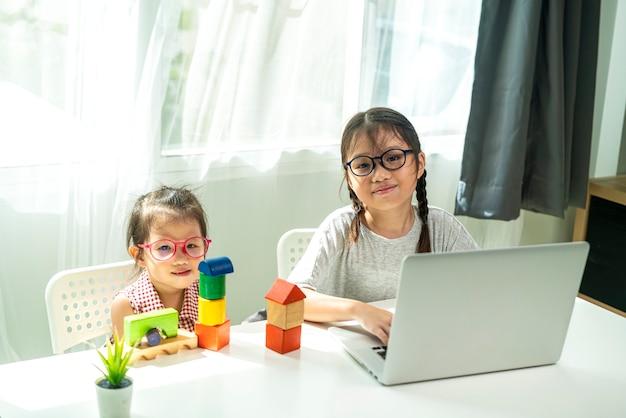 그녀의 여동생과 함께 집에서 홈 스쿨링 온라인 학습을 하 고 아시아 소녀