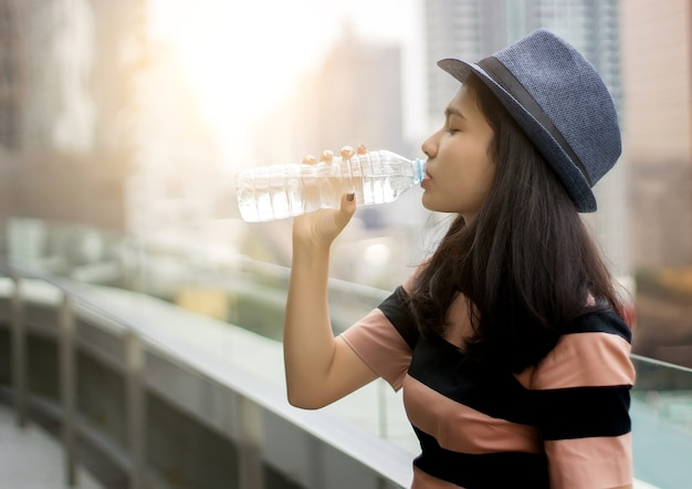 Asian girl drinking water from bottle in morning light