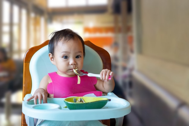 Asian girl eating food on baby table food.
