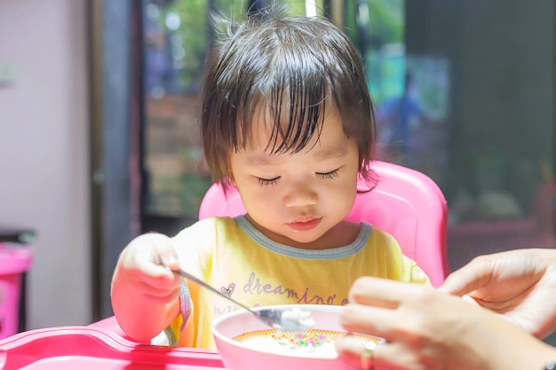 Asian girl eating fried sausages in the aluminium bowl near window at home