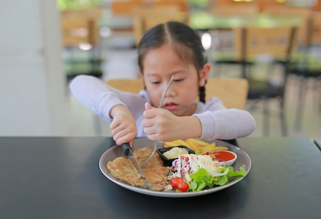 Asian girl eating pork steak and vegetable salad on the table.