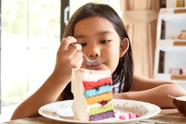 카페에서 케이크를 먹는 아시아 소녀.