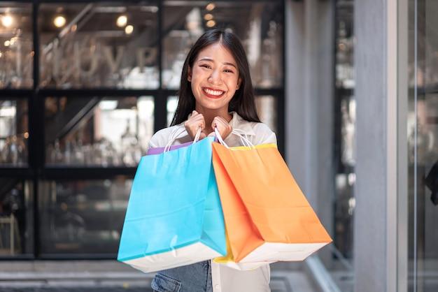 アジアの女の子は、買い物袋を持って幸せな笑顔で美しい女の子を興奮させたリラックスした表情