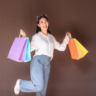 アジアの女の子は、リラックスした表情で買い物を楽しんで買い物袋を保持している美しい少女を興奮させた