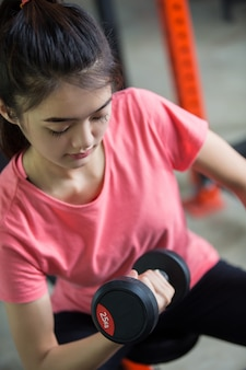 Asian girl exercising in the gym, she lifted the dumbbell she has committed.