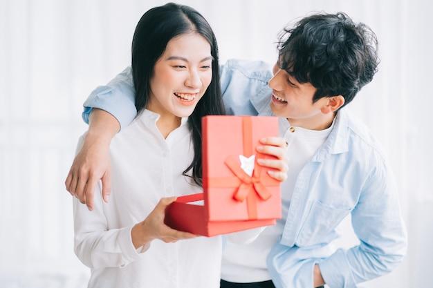 アジアの女の子はバレンタインデーに彼女のボーイフレンドからの贈り物を受け取ることに幸せと驚きを感じています
