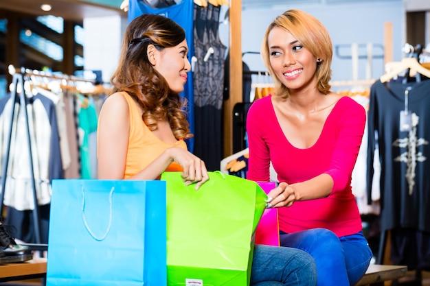 バッグでお互いに購入を示す店で買い物をしているアジアのガールフレンドのファッション