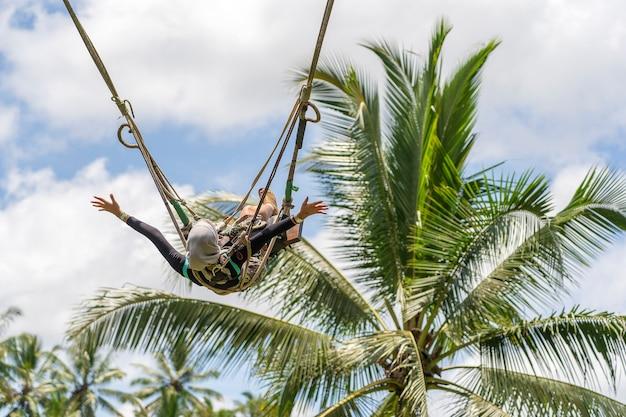 ジャングルの中でスイングを楽しんでいるアジアの女の子。インドネシア、ウブド近郊の田んぼにあるバリ島の熱帯雨林で揺れる人々