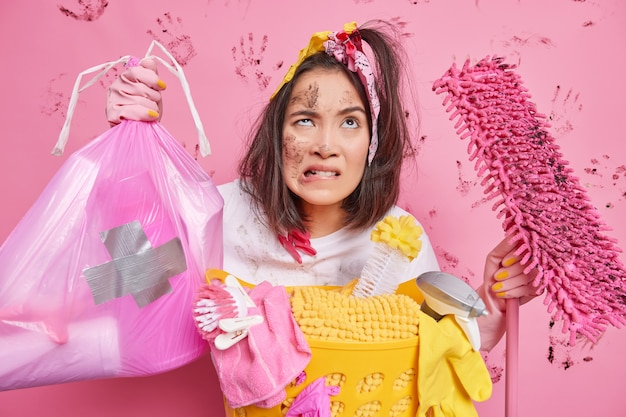 Asian girl helps mother to do work about house holds garbage bag dirty mop has frustrated tired face expression looks upwards stands near basket with detergents and laundry