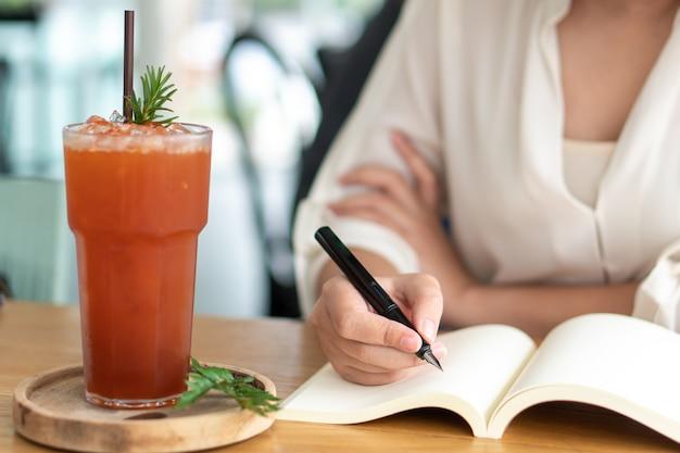 空の本に書く黒いペンを持つアジアの女の子。日記ライティングストーリー