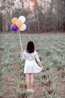 Asian girl holding balloons in a field.