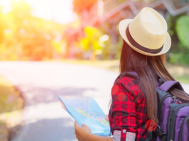 道路と森林のバックパックで地図を保持しているアジアの女の子の背景。