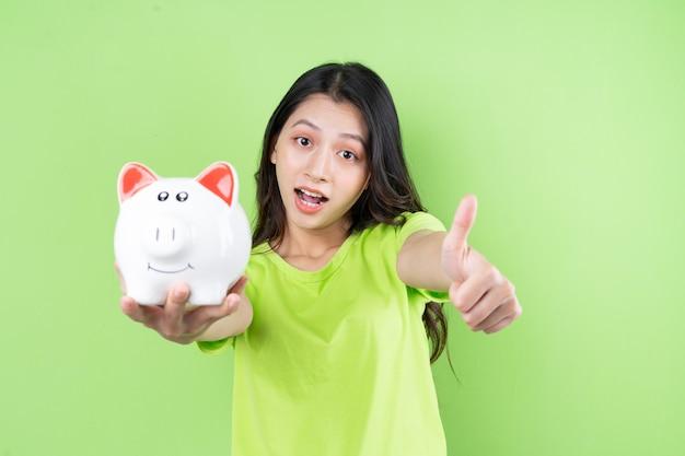 彼女の手で貯金箱を保持しているアジアの女の子お金節約の概念