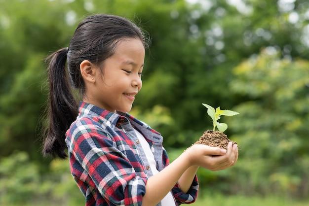 植物と土壌を保持しているアジアの女の子