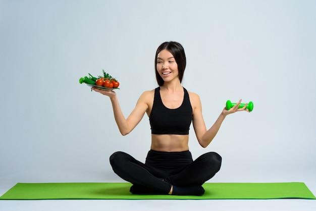 Asian girl holds dumbbells and plate of veggies.