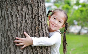 Asian girl hugging a tree with her arms
