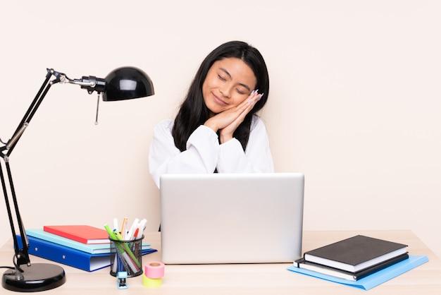 Bedorable 식 베이지 색 벽 만들기 수면 제스처에 노트북과 직장에서 아시아 소녀