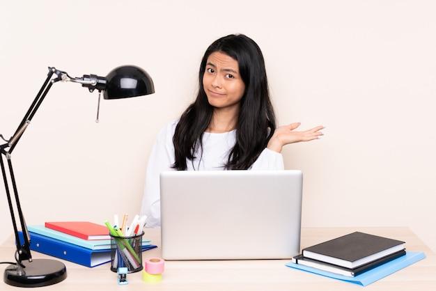 Азиатская девушка на рабочем месте с ноутбуком на бежевой стене недовольна, что-то не понимаю