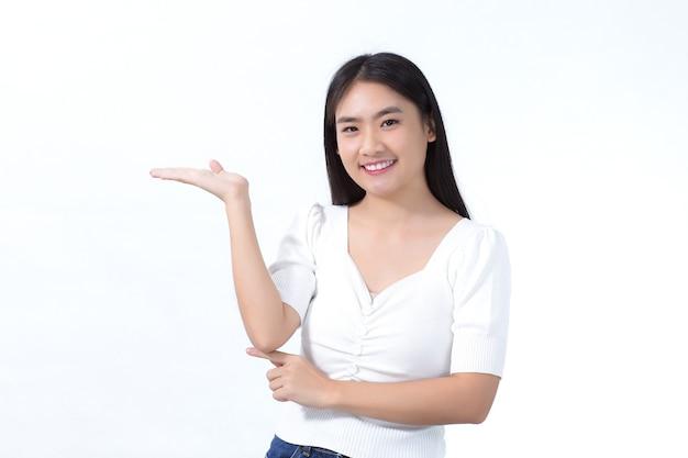 黒の長い髪のアジアの女の子は白いシャツを着て、白い背景に何かを提示するためにポイントを示しています。