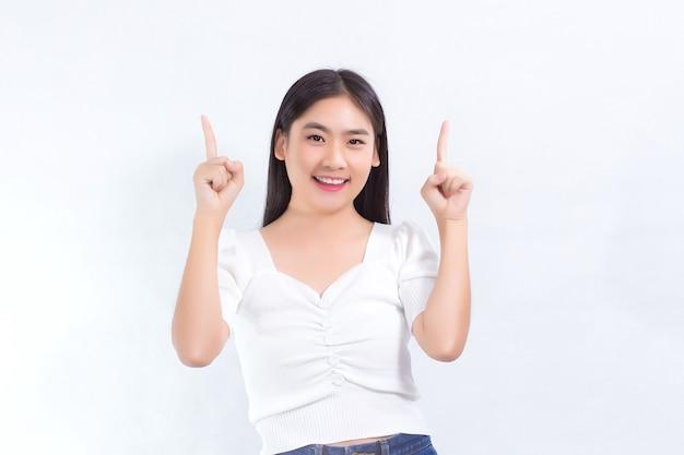 黒の長い髪のアジアの女の子は白いシャツを着て、何かを提示するためにポイントを示しています