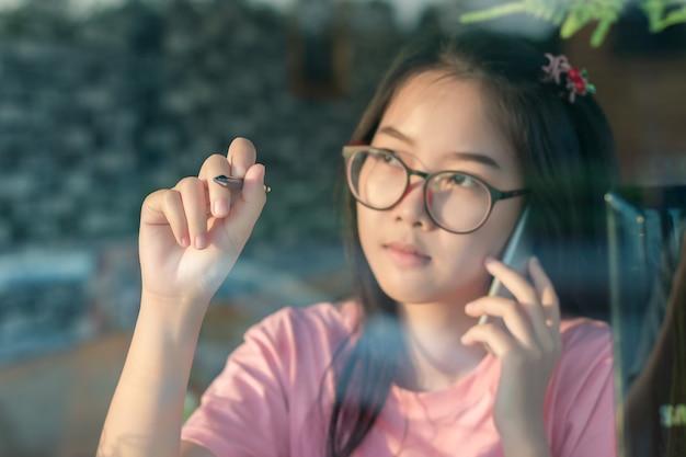 携帯電話で話しているメガネのアジアの女の子とコーヒーショップデスクでガラスに書く