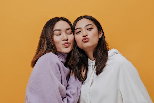パーカーのアジアの女の子はオレンジ色の壁にキスを吹く