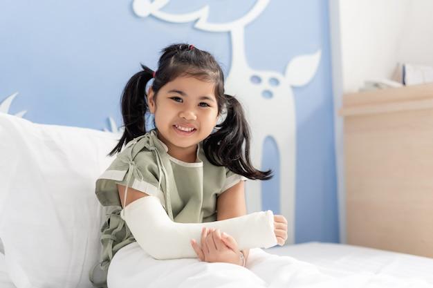 手術から戻って腕を骨折したベッドで横になっている病院でアジアの少女