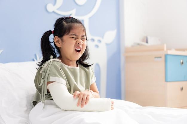 腕の骨折で痛いベッドの上の病院でアジアの少女