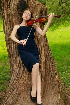 Азиатская девушка в природе со скрипкой. фото высокого качества