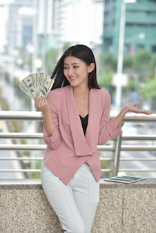ピンクのスーツでアジアの女の子現金を持って手に甘い笑顔を送ってください。