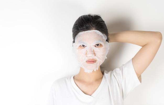 Азиатская девушка в надевании маски для ухода за кожей