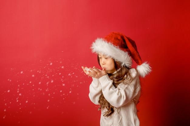 Азиатская девушка в новогодней шапке, дует снег на красном фоне