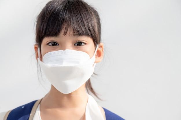白い背景のアジアの女の子は、コロナウイルス病の蔓延を防ぐフェイスマスクを着用しています。彼女の顔にサージカルマスクを持つ少女のクローズアップ