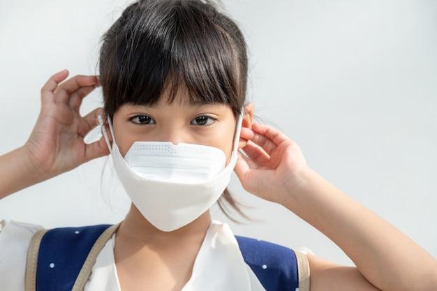 白い背景のアジアの女の子は、コロナウイルスの拡散から保護するフェイスマスクを着用しています