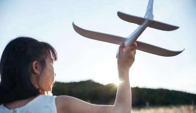 하얀 드레스를 입은 아시아 소녀는 일몰 때 들판에서 글라이더를 연주하고 야외에서 자연과 미래의 꿈을 즐기는 개념을 즐기고 있습니다.